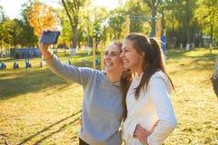 2 девушки фотографируют Selfie после тренировки в свежее под открытым небом Делающ спорт в утре и фото сообщают в inst Стоковые Изображения RF