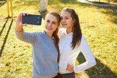 2 девушки фотографируют Selfie после тренировки в свежее под открытым небом Делающ спорт в утре и фото сообщают в inst Стоковое Фото