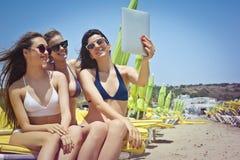Девушки фотографируя на пляже Стоковые Фотографии RF