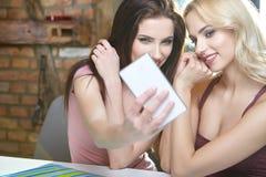 Девушки фотографируя на телефоне дома Стоковое Изображение RF