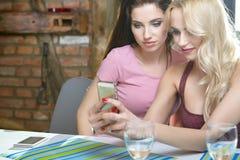 Девушки фотографируя на телефоне дома Стоковые Изображения