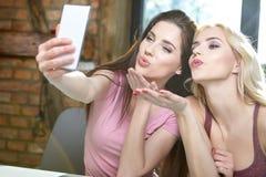 Девушки фотографируя на телефоне дома Стоковые Фотографии RF