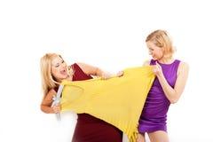девушки ходя по магазинам 2 платья стоковая фотография