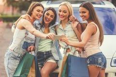 Девушки ходя по магазинам с автомобилем Стоковое Фото