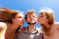 2 девушки целуя одного мальчика имея потеху внешнюю Стоковые Изображения RF