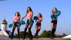 Девушки чирлидера с pompoms танцуют outdoors на backround неба акции видеоматериалы