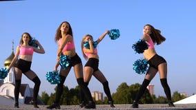 Девушки чирлидера с pompoms танцуют outdoors на backround неба сток-видео