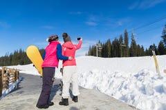 Девушки лыжи 2 женщин и горы снега зимы курорта сноуборда принимая фото Selfie умный телефон Стоковая Фотография RF
