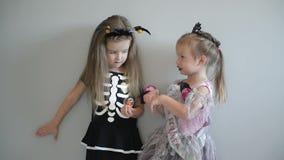 2 девушки Cutie в костюмах хеллоуина имеют потеху совместно костюмирует смешное изолировано видеоматериал