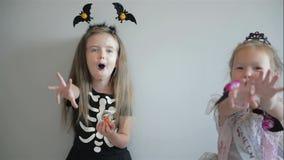 2 девушки Cutie в костюмах хеллоуина имеют потеху совместно костюмирует смешное изолировано сток-видео