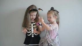 2 девушки cutie в костюмах хеллоуина имеют потеху совместно Смешные костюмы o видеоматериал
