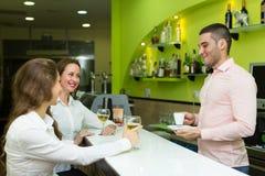 Девушки flirting с барменом Стоковые Изображения