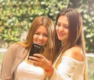 Девушки outdoors смотря телефон Стоковые Изображения