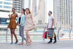 Девушки Shopaholics идут с приобретениями Красивые девушки в платьях Стоковая Фотография RF
