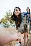 Девушки Trekking взбираясь концепция руки владением Стоковые Изображения RF