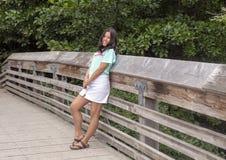 Девушки 13 yearold Amerasian представляя на деревянном мосте в дендропарке парка Вашингтона, Сиэтл, Вашингтоне стоковое изображение