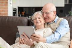 Деды используя социальные средства массовой информации на планшете стоковое фото