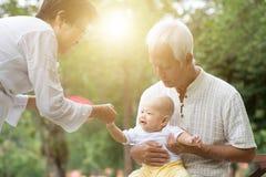 Деды принимая внука заботы outdoors Стоковая Фотография