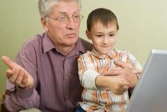 Дед и внук играя на компьтер-книжке Стоковые Фото