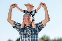 Дед носит мальчика малыша внука на его плечах Стоковые Изображения RF