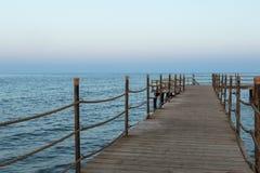 Дезертированная длинная старая деревянная пристань на времени захода солнца стоковые фотографии rf