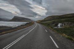 Дезертированная дорога асфальта бежать прочь в холмы, вдоль дороги водопад Стоковые Изображения RF