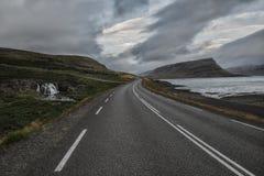 Дезертированная дорога асфальта бежать прочь в холмы, вдоль дороги водопад Стоковое Изображение