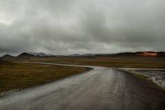 Дезертированная дорога асфальта бежать прочь в холмы Исландия Дух перемещения и приключения Стоковые Фотографии RF