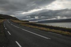 Дезертированная дорога асфальта бежать прочь в холмы Исландия Дух перемещения и приключения Стоковая Фотография