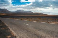 Дезертированная дорога с облаками Стоковые Фото