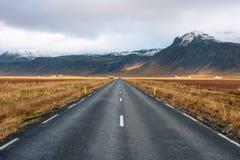 Дезертированная дорога Runnign через поля на ноге гор Volcaninc в Исландии стоковые изображения rf