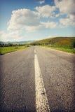 Дезертированная дорога водя к горам Стоковые Фото
