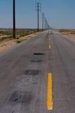 Дезертированная дорога в середине пустыни Стоковая Фотография RF