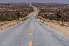 Дезертированная дорога в середине пустыни Стоковые Фото