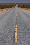 Дезертированная дорога в середине пустыни Стоковые Фотографии RF