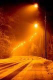Дезертированная дорога зимы загоренная к ноча освещает в желтом цвете Стоковое фото RF