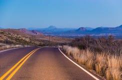 Дезертированная дорога изгибая к горам Стоковые Изображения RF