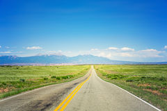 Дезертированная дорога долины идя к горизонту Стоковые Изображения