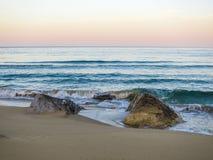 Дезертированный песчаный пляж на заходе солнца яблоко заволакивает вал солнца природы лужка ландшафта цветков Стоковые Фото