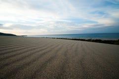 Дезертированный песчаный пляж с чистым точным песком на восходе солнца стоковое фото rf