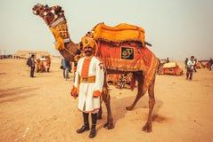 Дезертируйте ландшафт и индийский офицер с верблюдом во время фестиваля пустыни Раджастхана Стоковое Изображение