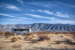 Дезертируйте располагаясь лагерем Airstream с горами в расстоянии стоковое фото