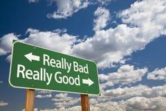 Действительно плохие, действительно хорошие зеленые дорожный знак и облака стоковое изображение