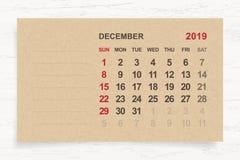 Декабрь 2019 - ежемесячный календарь на предпосылке коричневой бумаги и древесины иллюстрация вектора