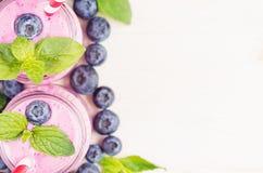 Декоративная граница фиолетового smoothie плодоовощ голубики в стекле раздражает с соломой, листьями мяты, ягодами, концом вверх, Стоковые Изображения RF