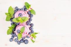 Декоративная граница фиолетового smoothie плодоовощ голубики в стекле раздражает с соломой, листьями мяты, ягодами, взгляд сверху Стоковое Изображение RF