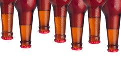 Декоративная картина загерметизированных пивных бутылок лагера с красными падениями эля и воды изолированных на белой предпосылке Стоковое фото RF