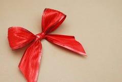 Декоративная красная лента смычка изолированная на предпосылке бумаги ремесла Скопируйте космос для текста Стоковая Фотография RF