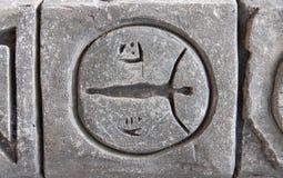 Декоративная серая каменная стена с символами и концом-вверх иероглифов Стоковые Фотографии RF
