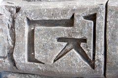 Декоративная серая каменная стена с символами и концом-вверх иероглифов Стоковое Изображение RF